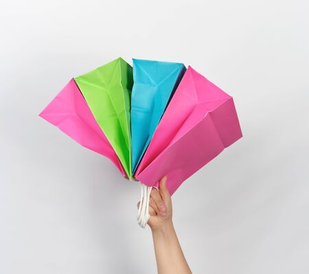 female hand holding four colored paper shopping packaging bags on white background, concept of seasonal sales