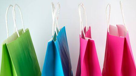 empty multi-colored paper shopping bags with white handles , close up