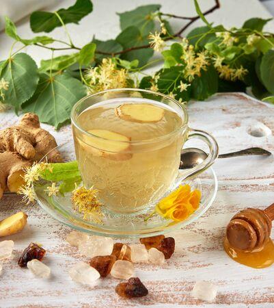 transparente Tasse mit Tee aus Ingwer und Linde auf einem weißen Holzbrett, Ansicht von oben
