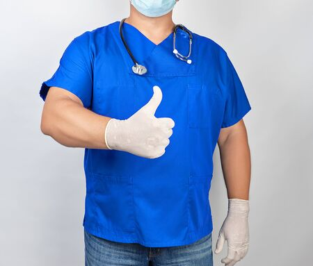 male doctor in blue uniform and latex white gloves shows right hand gesture like, thumb raised up