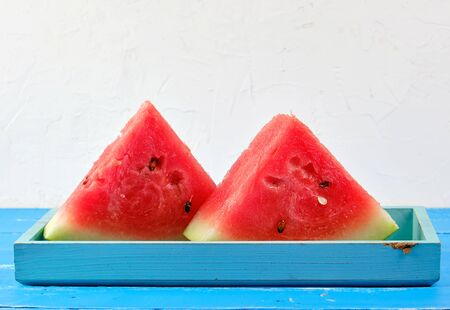 sliced triangles ripe red round watermelon with seeds on a blue background