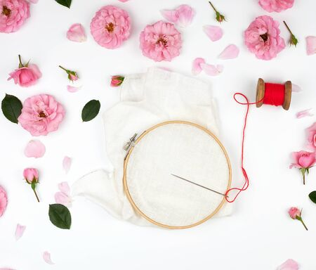 round wooden hoop and a red thread with a needle, concept of embroidery products, top view