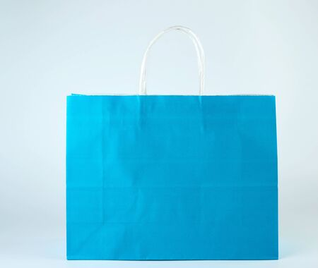 blue paper shopping bag with a handle on a white  background, close up