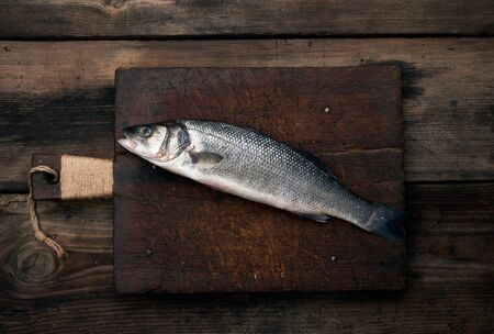 fresh whole sea bass fish on brown wooden cutting board, top view