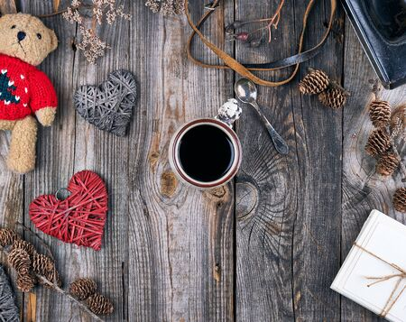 ceramic cup with black coffee and a little teddy bear in a red sweater, gray wooden background, top view
