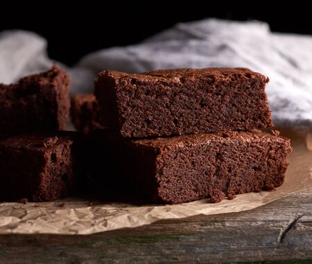 stack of baked square pieces of chocolate brownie cake on brown parchment paper, black background
