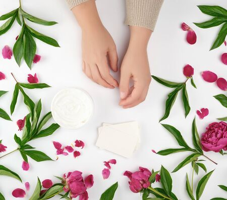 two female hands and a jar with thick cream and burgundy flowering peonies with green leaves, top view, concept of anti-aging procedures for rejuvenating and moisturizing the skin of hands Banco de Imagens