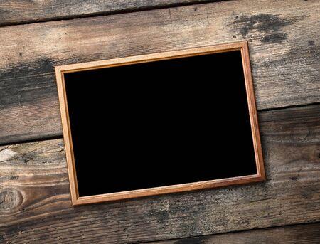 rechteckiger brauner Holzrahmen auf einem Hintergrund von sehr alten Brettern, leerer Raum
