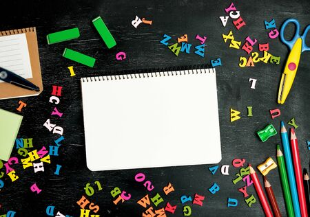 open spiral notebook with clean white sheets, wooden colored pencils, scissors on a black background, back to school backdrop