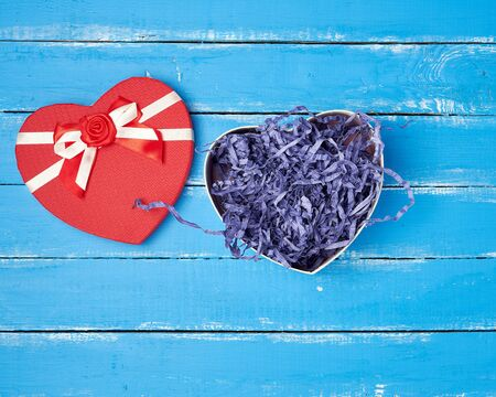 open red heart-shaped gift box with a bow on a blue wooden background, top view, festive backdrop