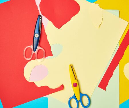 pair of plastic scissors and colored paper for cutting figures, application and scrapbooking