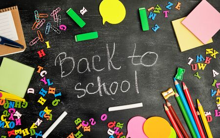 school supplies: multicolored wooden pencils, notebook, paper stickers, paper clips, pencil sharpener and white chalk inscription back to school on a black background, backdrop for schoolchildren