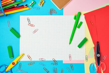 white squared paper from notebooks, wooden colored pencils, paper clips, scissors on a blue background, back to school