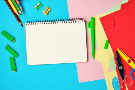 white squared  notebook, wooden colored pencils scissors on a blue background, back to school
