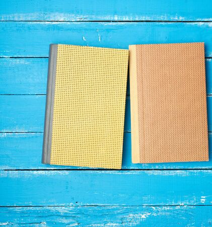 two closed hardcover books on a blue wooden background, flat lay