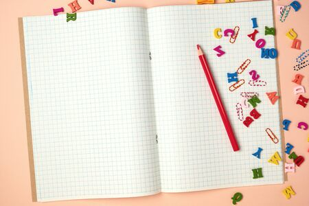 open checked notebook and red wooden pencil, back to school backdrop