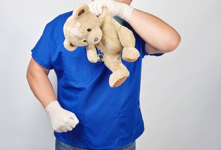 doctor in a blue uniform holding a teddy bear with a plaster near the head in a sign of despair,  concept of failure and sadness