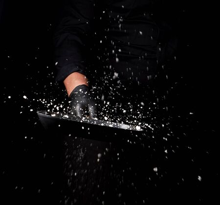 Chef in black uniform holds a pan with white salt and throws up, selective focus, blurred grains of seasoning 写真素材 - 128876043