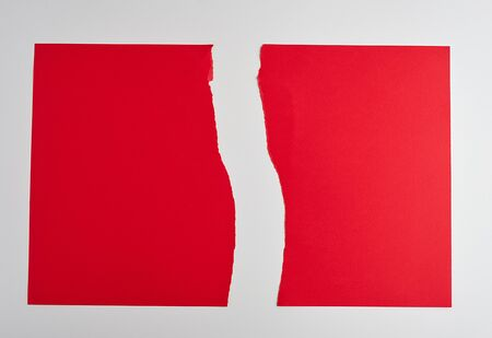 torn in half empty red sheet of paper on white background, close up
