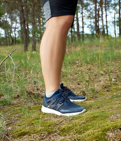 male legs of athlete runner in blue shoes in the middle of the forest, summer day
