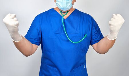 doctor in blue uniform and white latex gloves clenched his fists