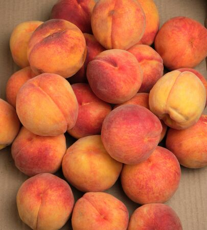 heap of ripe yellow-red round peaches, top view