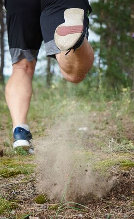 adult man in black shorts runs in the coniferous forest, concept of a healthy lifestyle and running in the fresh air