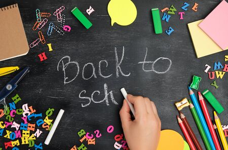 female hand writes with a white chalk on a blackboard back to school, around the perimeter of the school bright supplies, top view