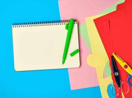 white squared  notebook, green pen and scissors on a blue background, back to school