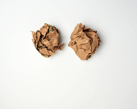 two crumpled sheets  of brown paper on a white background, close up, copy space
