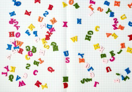 open notebook with white sheets in a box and small multi-colored wooden letters, back to school