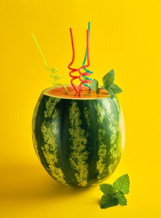 ripe striped green watermelon is cut and multicolored plastic cocktail tubes with a sprig of mint on a yellow background,  refreshing summer cocktail for a friendly company 스톡 콘텐츠