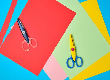 pair of plastic scissors and colored paper for cutting figures, application and scrapbook Stok Fotoğraf