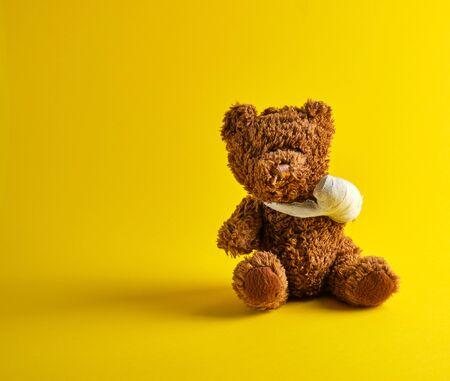 brown teddy bear with a bandaged paw sitting on a yellow background