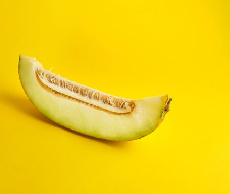 piece of ripe melon with seeds on a yellow background, copy space Stock fotó
