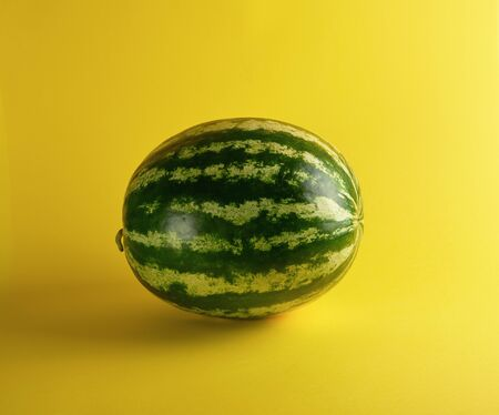 big green oval striped whole watermelon on a yellow background, summer berry