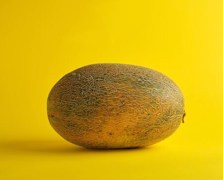 whole ripe melon on a yellow background, summer fruit, close up Stock fotó