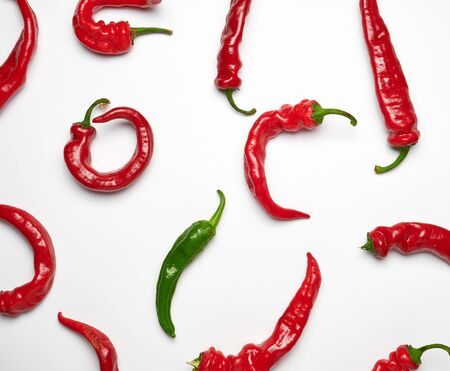 many red whole fruits of hot pepper and one green on a white background, concept of difference and discrimination