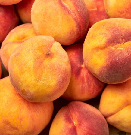 heap of ripe yellow-red round peaches, close up