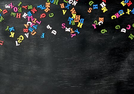 multicolored small wooden letters of the English alphabet on a black chalk board, copy space, back to school