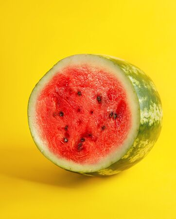 half round ripe red watermelon with brown seeds on a yellow background, summer berry