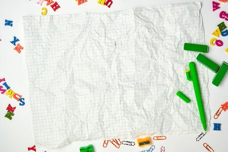 crumpled squared sheet of paper from a school notebook and a green pen, back to school