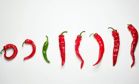 whole ripe red hot chili peppers on a white background, one green, concept of distinction and discrimination