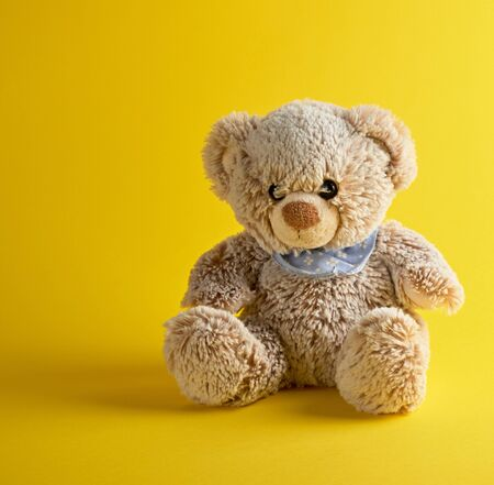 brown teddy bear sitting on a yellow background, copy space
