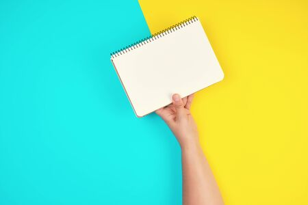 womans hand holds an open spiral notebook with blank white sheets on a yellow-blue background