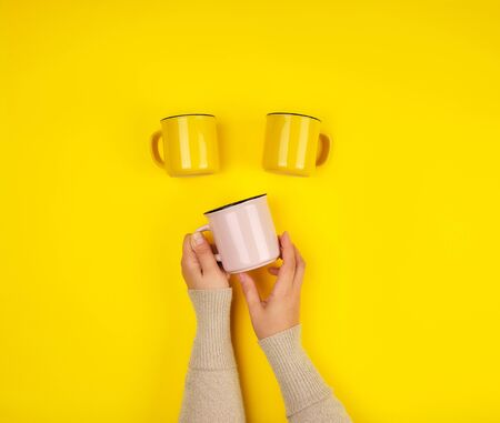 ceramic cups and female hands on a yellow background, copy space