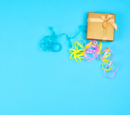 closed golden gift box with a bow on a blue background, top view, festive backdrop