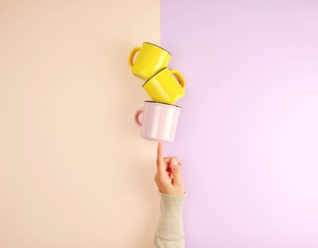 stack ceramic cups are supported by a female hand on a beige lilac background, copy space