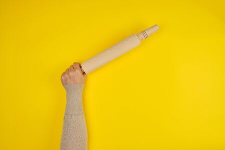 hand holding a wooden rolling pin on a yellow background, copy space Stock fotó