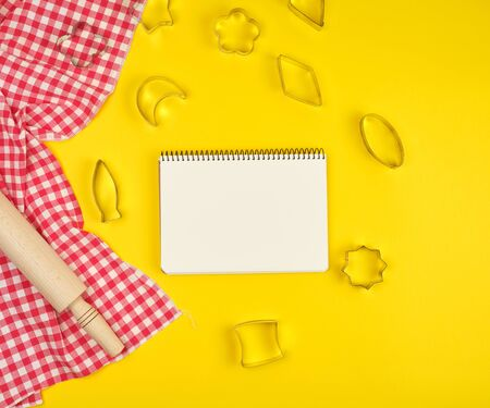 new wooden rolling pin on a red textile napkin and open notebook, yellow   background, top view Archivio Fotografico